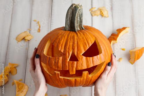 Fotografiet Woman carving big orange pumpkin into jack-o-lantern for Halloween holiday decor