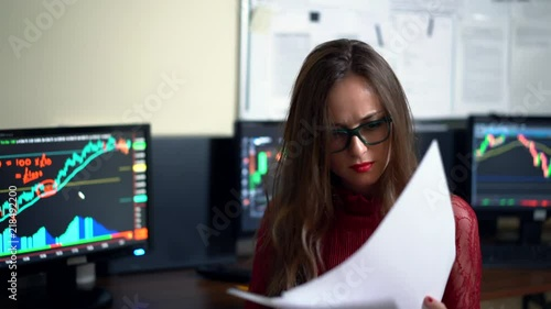 Finance advisor checking world trading profits. Brunette professional woman working with photocopies on the background of computers. Shot in 4K (UHD).