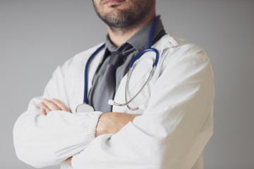 An unidentified doctor with a stethoscope around the neck crosses his arms