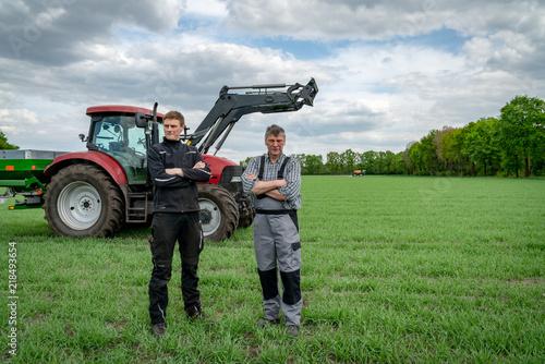 Fototapeta Ackerbau - Landwirt mit Sohn vor einem Traktor im Getreidebestand
