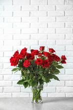 Vase With Beautiful Red Roses On Table Against Brick Wall Background