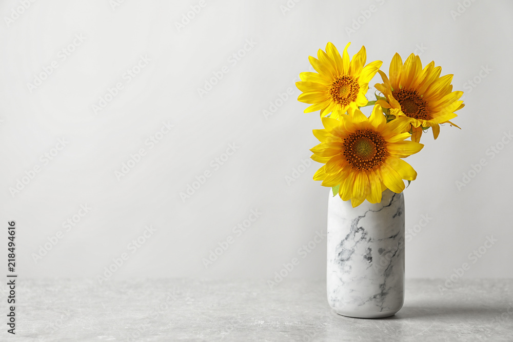 Vase with beautiful yellow sunflowers on table