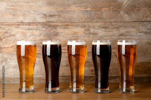Glasses with beer on table against wooden background Canvas Print