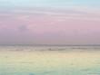 Pastel peaceful scene of a calm ocean sea and sunset sky.