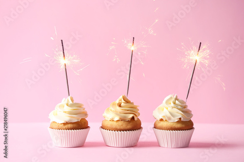Photo  Delicious birthday cupcakes with burning sparklers on color background