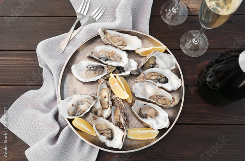 Fresh oysters with cut juicy lemon served on table, flat lay