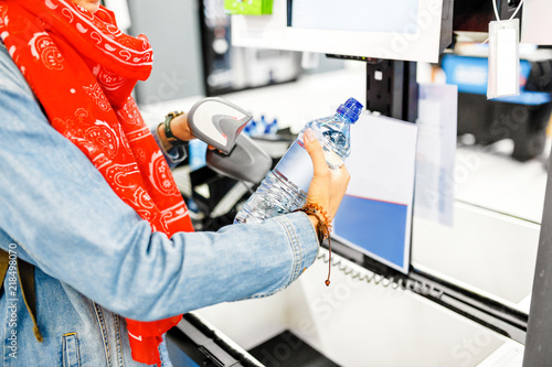 happy woman buying bottle of water at supermarket self service cash register check out