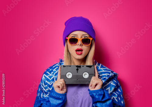 Fotografia  Young blonde girl in 90s sports jacket and VHS cassette on pink background