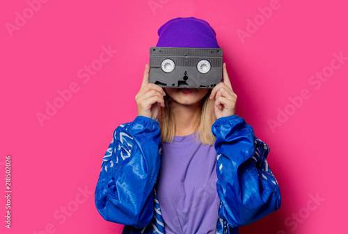 Papel de parede  Young blonde girl in 90s sports jacket and VHS cassette on pink background