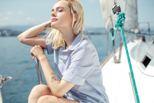 A Happy Beautiful Young Woman In Blue Shirt Sitting On The Side Of A Sail Boat On A Calm Blue Sea Enjoying Summer Vacation. Close-up.