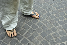 Dirty Feet Of A Man Wearing Flip Flops On The Old Stone Floor. Bologna, Italy
