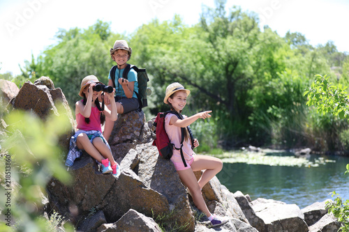 Little children with traveling gear outdoors. Summer camp