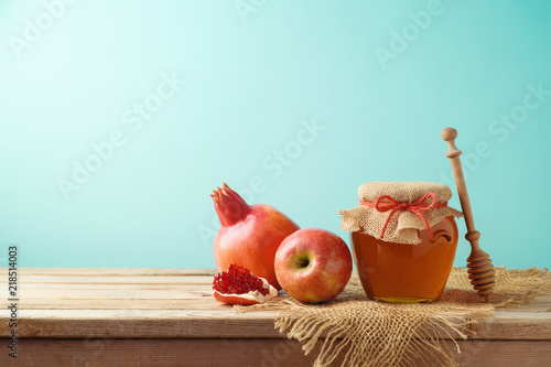 Jewish holiday Rosh Hashanah background with honey jar, apple and pomegranate on wooden table.