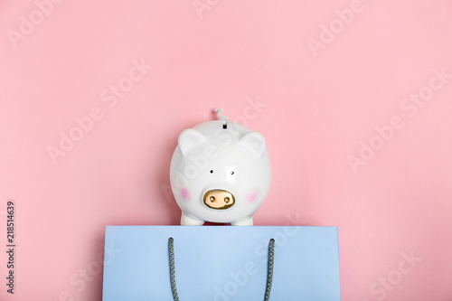 Valokuvatapetti Flat lay composition with shopping bag and piggy bank on color background