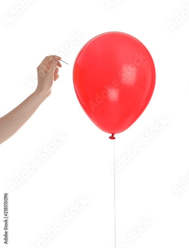 Fotografía  Woman piercing red balloon on white background