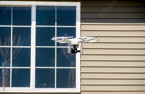 white drone with camera hovering by house window