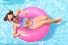 Little Girl With Inflatable Ring In Swimming Pool