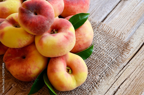 Chinese flat donut peaches with leaves on on old wooden table also known as  Saturn donut, Doughnut peach, Paraguayo.Healthy eating or diet concept.Selective focus.