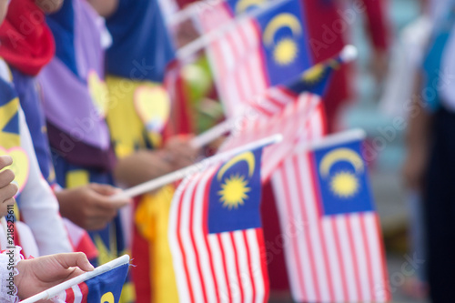Poster Kuala Lumpur Hand waving Malaysia flag also known as Jalur Gemilang in conjunction with the Independence Day celebration or Merdeka Day.