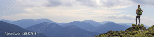 Back view of young slim girl with backpacks standing on rocky mountain top against bright blue morning sky enjoying foggy mountain range panorama. Tourism, traveling and healthy lifestyle concept.