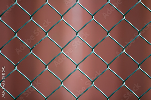 Close-up of isolated painted simple geometric black iron metal wire chain link fence eon dark red background Canvas Print