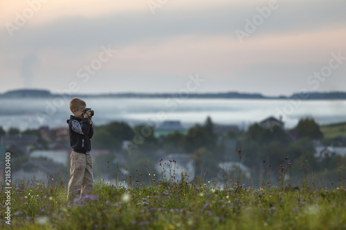 Poster Donkergrijs Young cute blond child boy with photo camera standing on grassy hill top on spring or summer day.