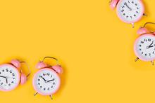 Pink Alarm Clock On Yellow Bac...