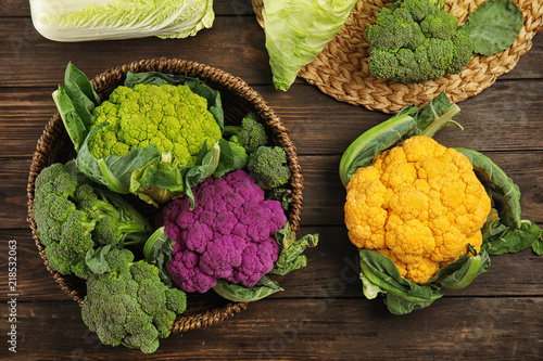 Different cabbages on wooden table, top view. Healthy food