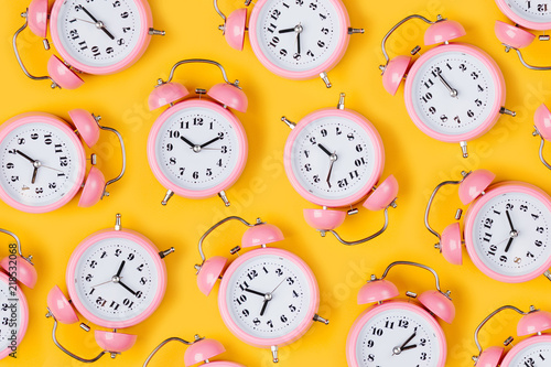 Fotomural Pink alarm clock on yellow background.