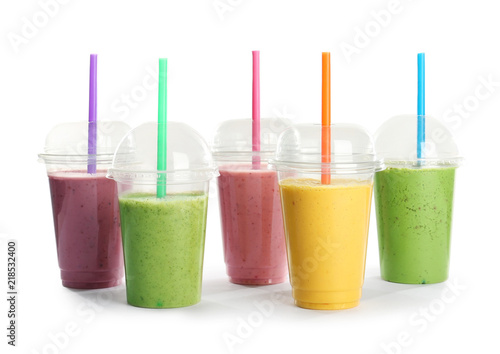 Plastic cups with fresh tasty smoothies on white background