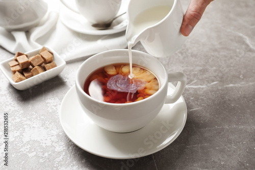 Foto auf Leinwand Kaffee Pouring milk into cup of black tea on table