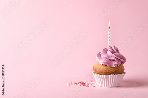 Photo  Delicious birthday cupcake with candle and space for text on color background
