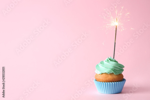 Photo  Delicious birthday cupcake with burning sparkler and space for text on color bac