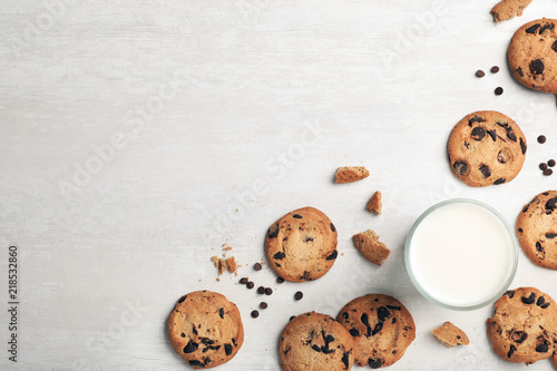 Flat lay composition with chocolate cookies and glass of milk on light background. Space for text