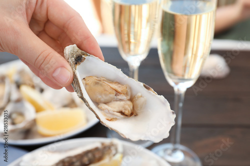 Woman with fresh oyster over table, focus on hand