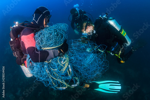 Fototapeta SCUBA divers attempting to remove a huge ghost fishing net tangled over a large area of a tropical coral reef obraz