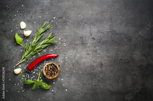 Tuinposter Hot chili peppers Selection of spices herbs and greens on black top view.