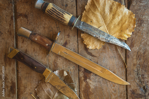 Three hunting knives on old wooden background with autumn leaves