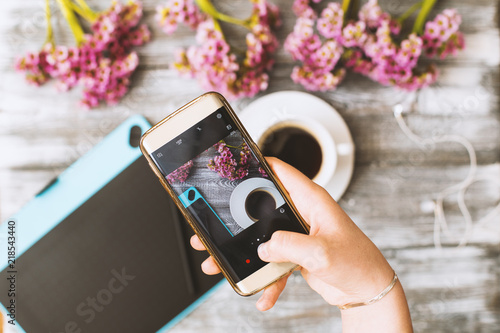 Instagram photographer blogging workshop concept, hand holding phone and taking photo of stylish flowers, cup of coffee and graphic tablet on grey wooden rustic background.space for text.