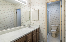 Interior Of Dated 1980s Home Bathroom With Single Sink And Toilet.
