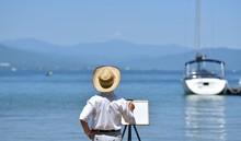 夏の湖畔・のんびりと絵を描く男性