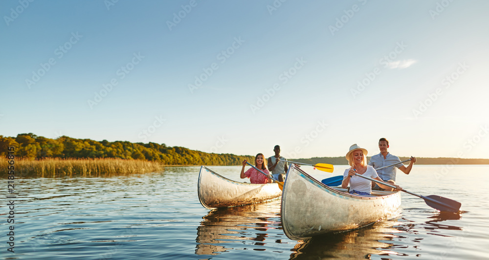 Fototapety, obrazy: Smiling young friends canoeing together on a lake in summer