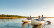 canvas print picture - Smiling young friends canoeing together on a lake in summer