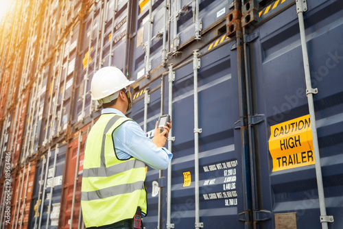 Wallpaper Mural Foreman control loading Containers box from Cargo freight ship, Warehouse shipping transportation concept