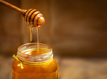 Honey In A Glass Jar With Hone...