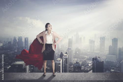 Photo  Asian businesswoman with red cape against modern city background