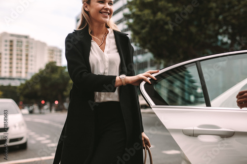 Smiling woman commuter getting out of a taxi Canvas Print