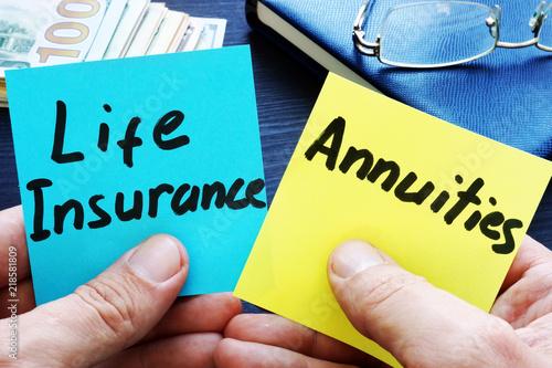 Man holding memo sticks. Life Insurance vs. Annuities. Wallpaper Mural