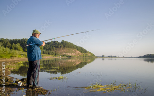 Fotobehang Vissen a man on a summer clear day, in a blue T-shirt with a fishing rod, stands on the river bank and catches fish