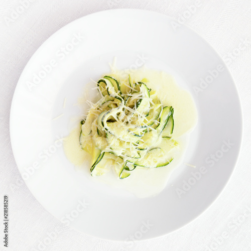 Photo zucchini fettuccine with creamy alfredo sprinkled with cheese